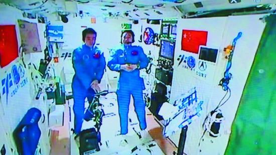 """11月15日,景海鹏(右)和陈冬在天宫二号首次接受""""天地采访""""。新华社发"""
