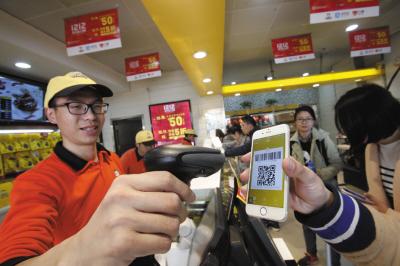 """消费者在超市里手机扫码参与""""双12""""活动。"""