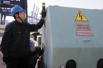 工作人员正在给船对接岸电。