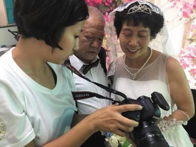 大学生正在给许阿姨和姜大叔选照片。