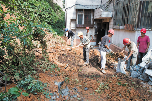中山区山屏花园36号居民楼门坍塌边坡已修复加固完毕,图为工人们正在清运现场残土。高士军摄