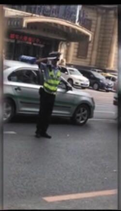 民警通过敬礼劝导违停车辆离开。