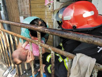 ▲消防员用扩张器对栏杆扩张救孩子。