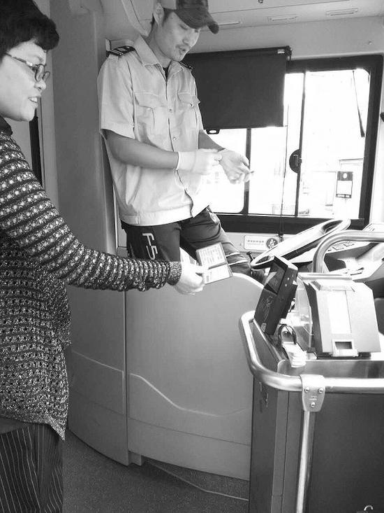 市民出示行驶证乘坐公交车。