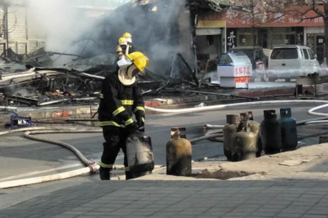 简易房起火 消防员抢抱液化气罐