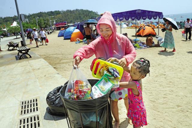 母女俩骄阳下运垃圾 游客素质提高浴场干净不少