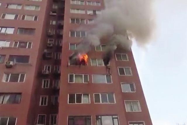 女子挂在8楼窗外 大连多警联动上演火场救人