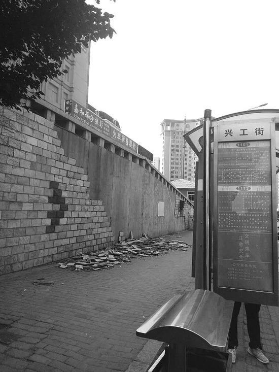 这面挡土墙附近正是兴工街公交枢纽站,过往行人很多。