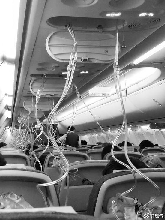 客舱的氧气面罩落在乘客眼前。图片来自微博