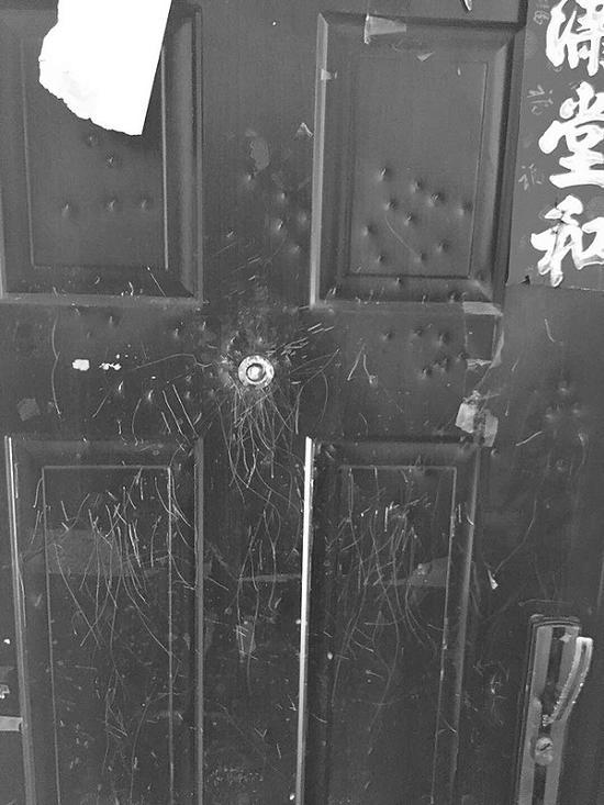 小李家的房门已经被砸得伤痕累累。
