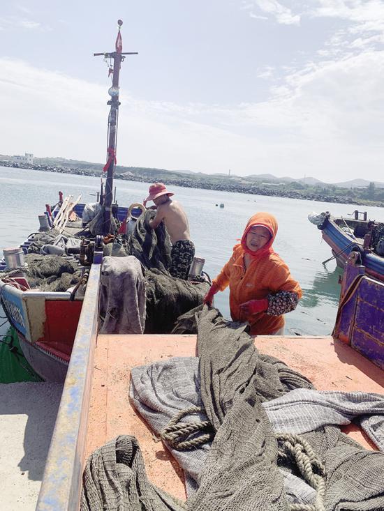 夫妻俩从自家的车上把网卸到渔船上,做好准备就可以出发了。