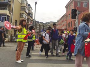 红灯亮了,义工拦住车辆,孩子与家长通行。