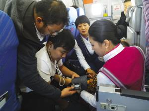 在机舱狭小的空间里,海南、大连两位医生与空姐配合救人。(左一为大连医生,左二为海南医生)郭晗 摄