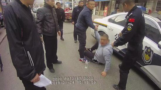 辅警张东恒将制服的杀人嫌疑人交给赶来的民警。