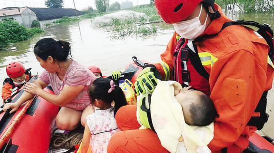 消防员推着冲锋舟,救出被困一家四口。