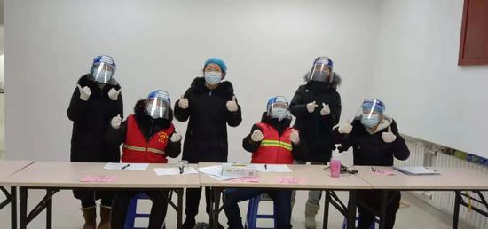 ▲王超(左三)和同事们一起投入到核酸检测采样登记工作中