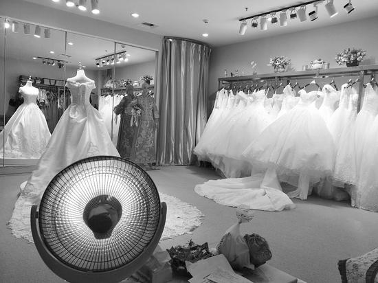 """婚庆广场的商户出示取暖费的收据,虽然交了钱,却不得不用""""小太阳""""取暖。半岛晨报"""