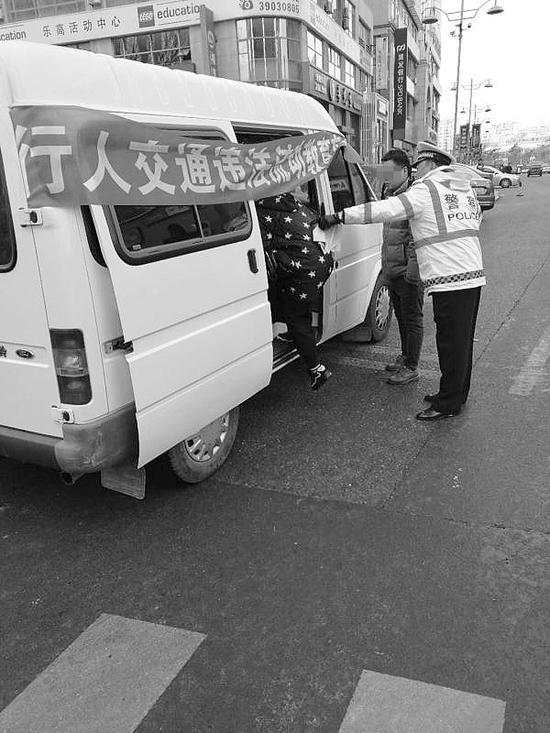 违法行人被请上流动宣教车。