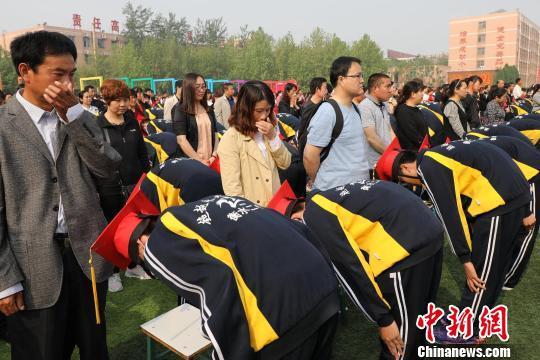 学生们在成人礼上为家长行拜谢礼。 崔广义 摄