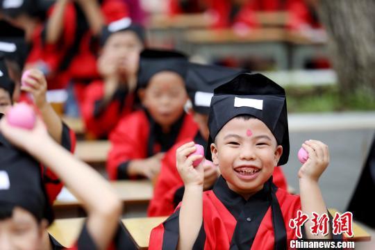 一年级新生展示老师发的红鸡蛋。 谭凯兴 摄