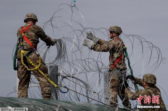 当地时间11月2日,美国得州Hidalgo,美国士兵在美墨边境安装铁丝网严防移民入境。