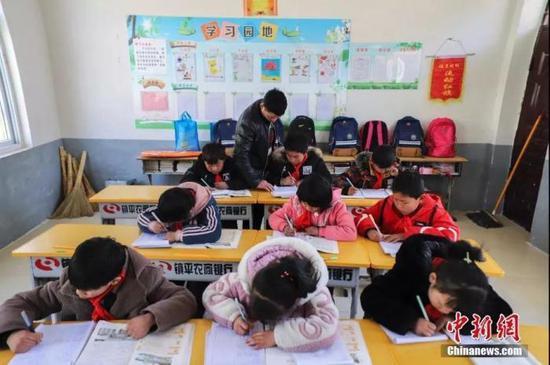 老师在教室里给小学生们辅导作业