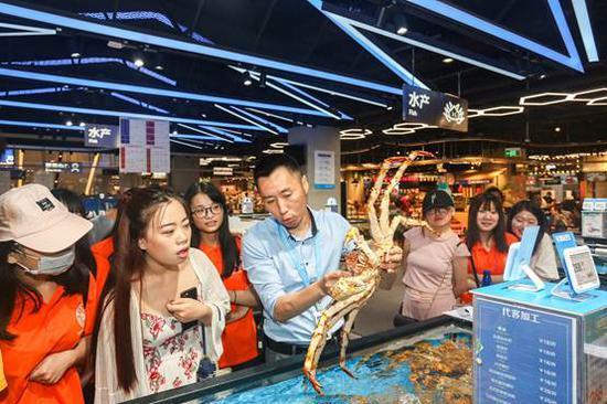 阿里商学院的学生们参观盒马鲜生,对盒马智能仓库拣货员这一新工种非常感兴趣