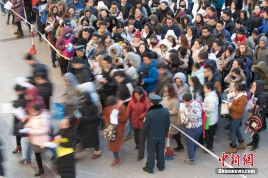 资料图:一公务员考点,考生排队准备进入考场。 中新社记者 武俊杰 摄