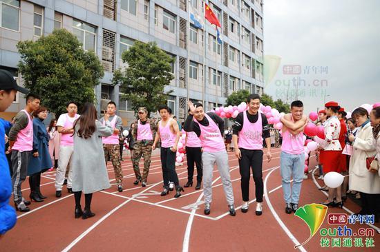 图为男老师起跑前做热身运动。学校供图