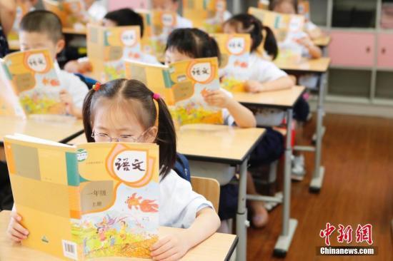资料图:孩子们正在认真阅读《语文》教材。 殷立勤 摄