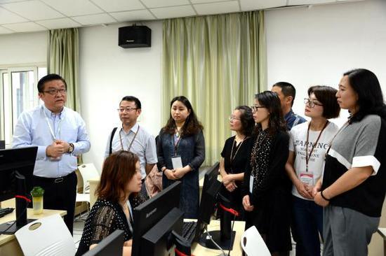 周宏(左一)向家长代表解析语文作文的评阅过程。 李立基 摄