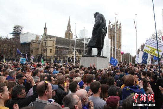 """资料图:3月23日,在欧盟同意英国延迟脱欧、英国脱欧前景仍面临""""灾难的不确定性""""困境之际,伦敦市中心举行了大规模呼吁举行""""第二次脱欧公投""""的示威游行。分分彩大发快三最稳计划图为人群聚集在市中心议会广场,在英国历史上杰出政治人物丘吉尔塑像下,期盼获得掌握未来命运的权利。中新社记者 张平 摄"""