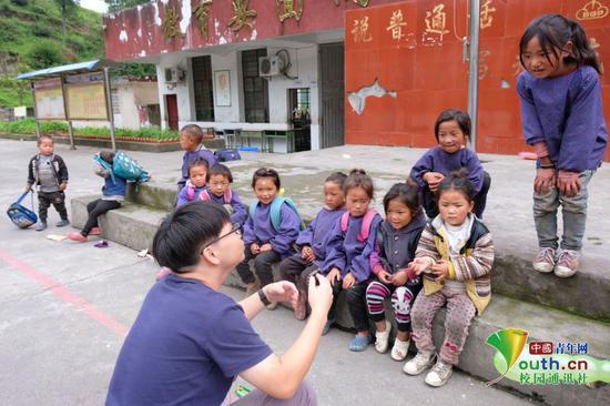 体育课上,队员正在和孩子们讲解篮球、羽毛球、乒乓球等运动知识。中国青年网通讯员 杨雨桐 摄