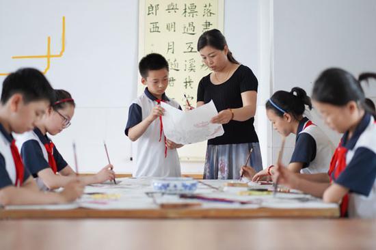 一位老师在指导学生练习国画创作-朱旭东-摄