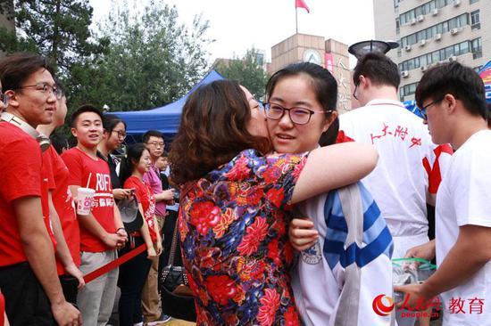 2019年高考首日,家长深情拥抱即将进入中国人民大学附属中学考点的孩子。 卢静摄