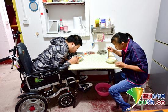 黎际勤与母亲在学校家属楼的宿舍里吃饭。中国青年网通讯员 李谌涵 供图