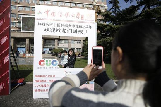 中国传媒大学迎来65周年校庆,校友们在纪念板前拍照留念。