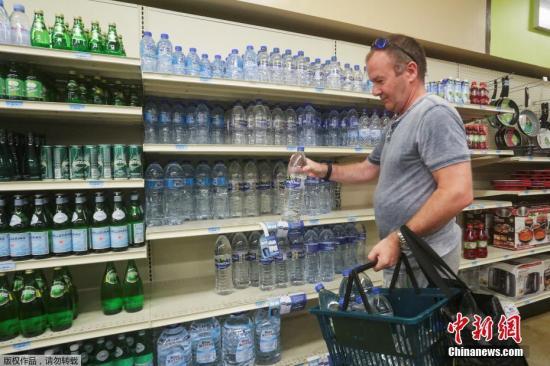资料图:人们在超市采购生活用品和水。