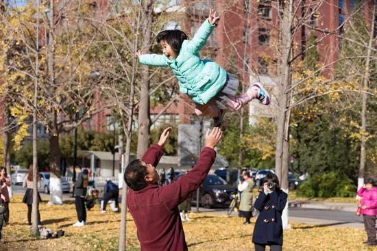 """""""来,飞高高!""""西风把孩子举高"""