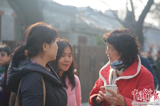 2月23日,中央戏剧学院,考生家长在学校门外等考生时,拿起手机分享备考经验。实习生王艺霏/摄