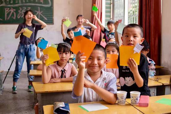 江西财经大学星光支教服务队在衙前中心小学支教,为孩子们教授折纸技能,孩子们正争先展示自己的作品。危雁冰/摄
