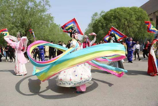 锣鼓声中京剧系学生翻着水袖、挥动旌旗登场