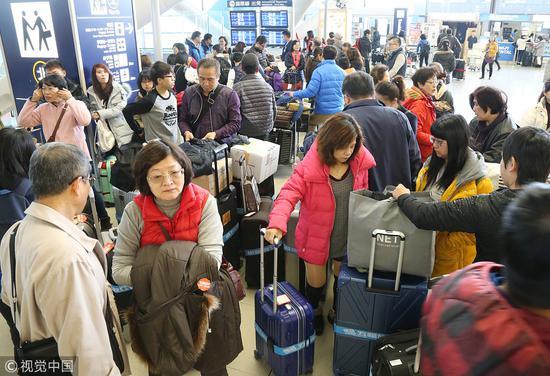 在大阪机场,准备登机的中国游客。(视觉中国)
