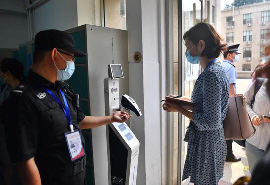 進入高考數學評卷點的工作人員首先進行體溫檢測。新京報記者 李木易 攝