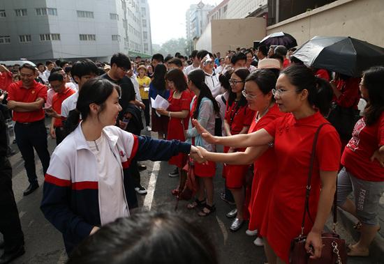 6月7日,北京陈经纶中学高考考点,身着红色衣服的老师与即将进入考场的考生们拉手鼓劲。当日,2019年全国高考正式拉开大幕,超千万考生奔赴考场。