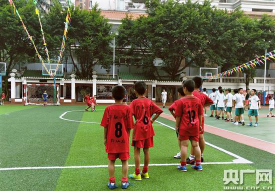 华融小学学生放学后在足球场上踢球。(央广网记者 王启慧/摄)