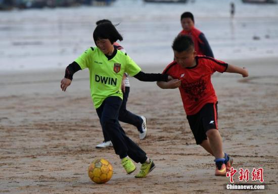 资料图:球员正在沙滩上踢比赛。中新社记者 王东明 摄