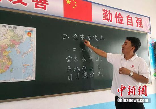 杨锋教孩子认字。