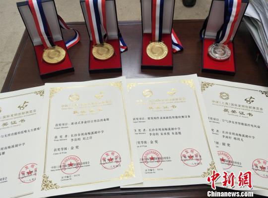 在2018年第二届中国(上海)国际发明创新展览会上,周南梅溪湖中学的4项学生发明获奖。图为奖牌和获奖证书。 刘曼 摄