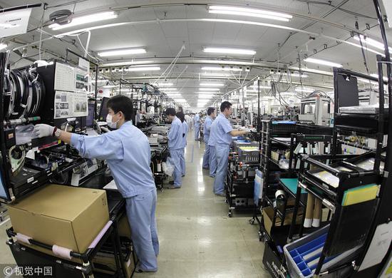 工人们在日本NEC无线网络公司工厂装配LTE设备。(图片来源:视觉中国)